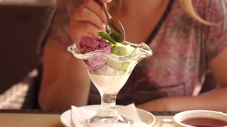 creme : Close-up of a girl eating ice cream from a beautiful glass in a street cafe. Slow motion.