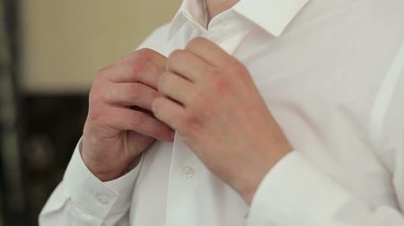 mandzsetta : People, business, fashion and clothing concept - close-up of man dressing up and fastening buttons on shirt at home. Man buttoning his shirt.