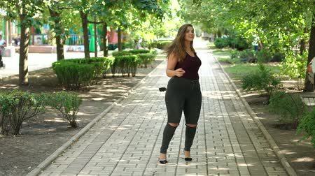 nagy : A young happy girl with excess weight walks in a summer park, she swims around herself and enjoys warm weather. Plus size model. Stock mozgókép