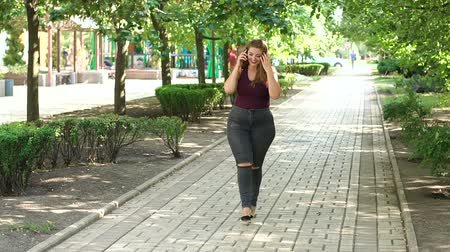 artı : A young girl with excess weight walks in the Park in the summer and talking on the phone. Fat woman in jeans in the Park with a phone.