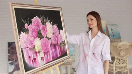 piwonie : A talented girl artist is admiring her painting in the drawing studio. Portrait of an artist girl near a picture with flowers of peonies.