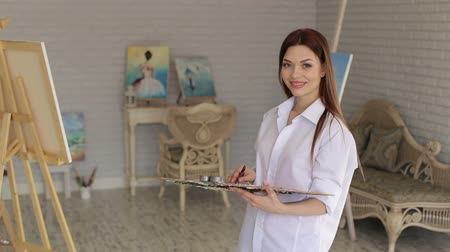 разорвал : Portrait of a cute young girl in a white shirt with a palette of colors in her hands in an art studio.