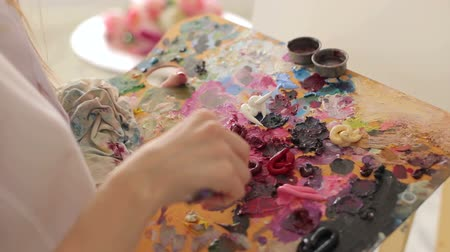 oilpaint : The artist mixes oil paints on a palette with a brush, close-up. Art.