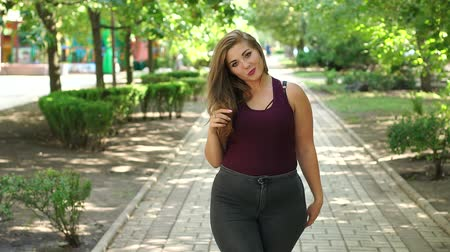 Футболка : Uncomplexed young girl overweight posing in the Park in the summer among the green trees. Plus size model. Girl XXL.