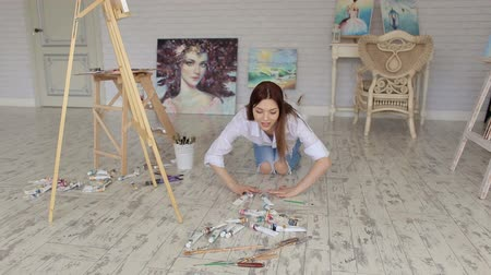 разорвал : A talented girl artist in a white shirt and torn jeans throws tubes of oil paint on the floor in the Studio for drawing. Стоковые видеозаписи