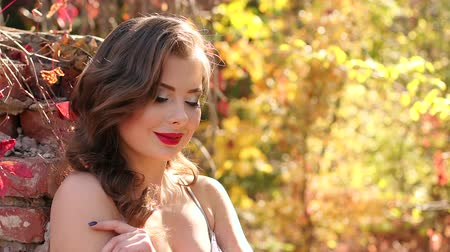 penteado : A young beautiful girl in an evening tight dress with an old hairstyle and bright make-up in an old abandoned Park in the autumn stands next to a brick wall. Model posing in the autumn Park.