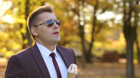 frontal : Successful young businessman walks in the autumn Park and eats ice cream. Portrait of a successful handsome man in a suit and sunglasses in a Sunny autumn Park with ice cream.