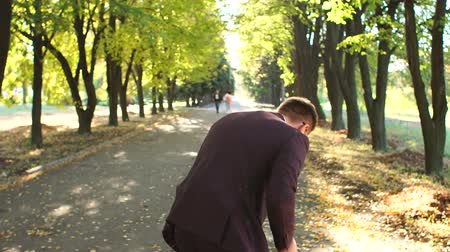 mellow autumn : A successful happy businessman in a suit dancing in the autumn Park enjoying success in business or victory. Winning dance businessman in the autumn Park at sunset. Slow motion.