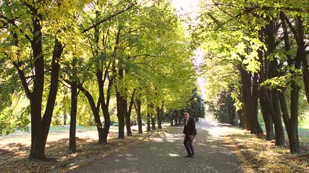 mellow autumn : A successful cheerful businessman in sunglasses and a suit dances and jumps in an autumn Park. Successful business concept. Slow motion. Stock Footage