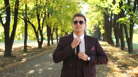buttoning : A handsome successful businessman in a suit and sunglasses stands in an autumn Park and straightens his tie.