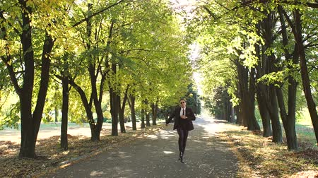 mellow : A successful cheerful businessman in sunglasses and a suit dances and jumps in an autumn Park. Successful business concept. Slow motion. Stock Footage
