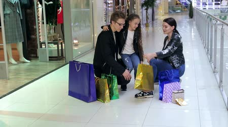 бакалейные товары : Joyful happy family looking at their shopping in the store, they hug in Mall. A variety of colorful packs stand beside him. Happy family holding packages and walking around mall while having shopping.