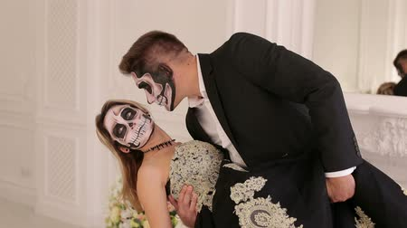 şeytan : Luxury young couple with halloween skull make-up in a dress and costume in a white room with vintage interior. Halloween face art. Halloween couple, woman and man with skull make-up. Stok Video