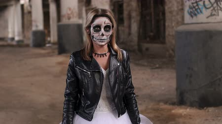 deadly : The girl in a wedding dress and in a leather jacket with a terrible make-up in form of a skull stands against the background of an abandoned train station with columns painted with graffiti. Halloween
