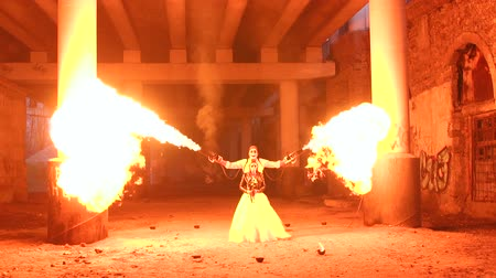 karanlık : A man with makeup skeleton Halloween holding two torches with a strong flame. Fire show. Halloween. Stok Video