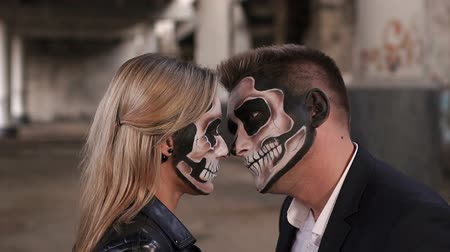 muertos : Close-up of the face of a couple in love with Halloween makeup in the form of a skeleton, they look at each other terrifyingly. Halloween loving couple with skull makeup looking at each other. Stock Footage