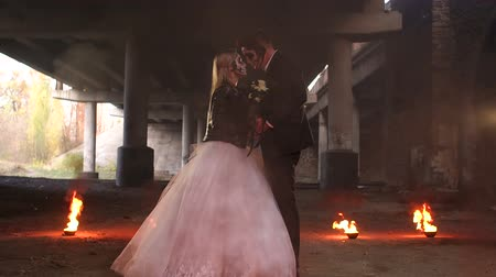 zombi : Scary couple with creepy makeup on Halloween with fire and burning torches in an abandoned mansion. Zombie bride and groom. Halloween and fire.