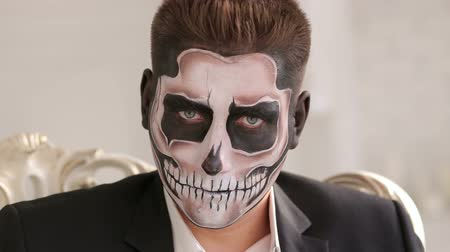zombi : Businessman with make-up skeleton sitting in the old grey chair, and creepy looking at the camera. Halloween or horror theme. Dead face make up portrait of young man in studio. Stok Video