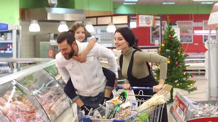 supermarket shelf : Merry happy family make purchases in the store for the Christmas holidays. The little daughter is sitting on her dads back, and they carefully look at the counter.