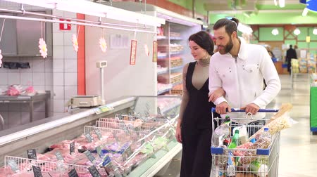 chladič : Food, sale, consumerism and people concept - happy couple with shopping cart buying meat at grocery store or supermarket. Positive smiling family couple choosing chilled meat in food store.