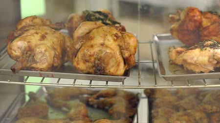 plivat : Industrial grill with chickens on rolling spit in cafe. Grilled chicken at a store. Grilled Chicken. Grilled chicken is sold in container at market.