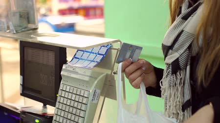 supermarket food : Close-up of woman holding credit card in hands at checkout counter in supermarket. Woman puts shopping in a package at the checkout in the grocery store.