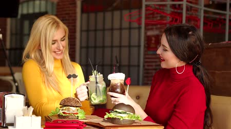 elegant dessert : Two happy girls, a blonde and a brunette, sit in a cafe in bright sweaters and clink glasses with cocktails. Two smiling girls drink cocktails and eat burgers in a bright restaurant.