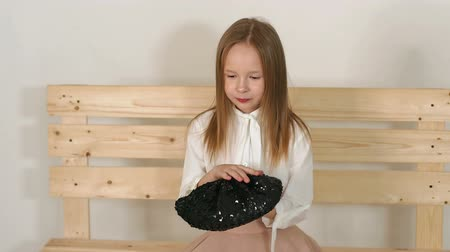 nevinný : A cute little girl is sitting on a wooden bench made of pallets in the studio against the background of a white wall, she is holding a black hat with sequins in her hands. Slow motion. Dostupné videozáznamy