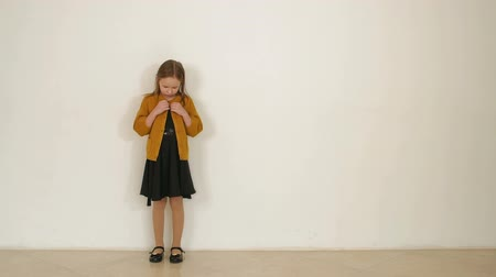 buttoning : A little charming girl stands against a white wall in a black dress and a brown sweater, she fastens the buttons on the sweater. Slow motion.