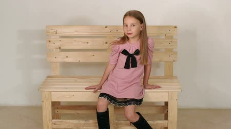 into the camera : A little cute girl in a pink dress and black boots sits on a wooden homemade bench in the Studio against a white wall. Little girl model posing in the Studio. Slow motion.
