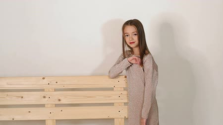 palety : A little cute smiling girl with blond hair and big brown eyes posing in the Studio on a white background near a wooden eco-bench. Slow motion.