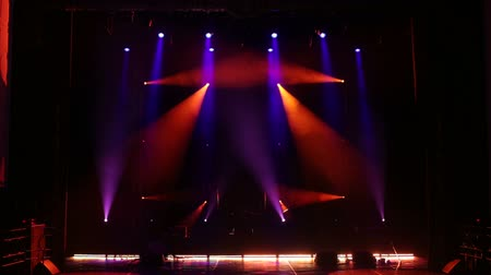 üretim : Multicolored rays on an empty stage in the dark. Stage lighting. Light show. Different color spotlights on empty stage with musical instruments and drum set. Stok Video