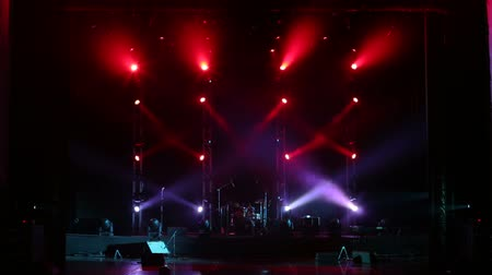 rock festival : Alternately flashing red and purple spotlights during a concert on stage. Concert lighting and equipment. Musical instruments in the dark on stage before the concert.