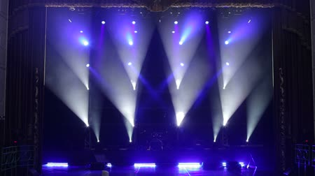 music band stage : Blue light flashing and white rays on an empty stage in the dark. White and blue professional spotlights on stage at a music concert. Stage lighting. Light show.