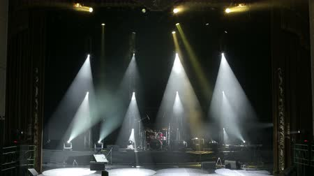music band stage : Blue light flashing and white rays on an empty stage. White and blue professional spotlights on stage at a music concert. Stage lighting. On stage there is a concert musical equipment, drum set. Stock Footage