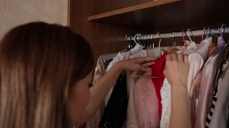 dvojčata : Young slender girl chooses clothes in the closet in the bedroom standing in front of a large mirror, close-up.