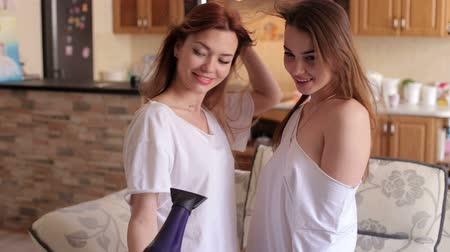 friendship dance : Two cheerful girls girlfriends in pajamas dry their hair with a hairdryer sing in it and dance.