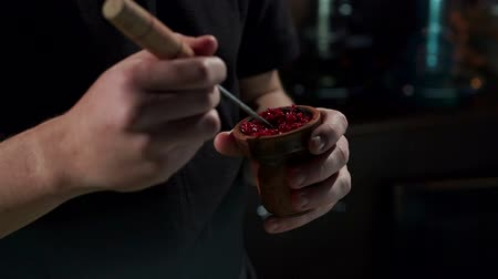 mouthpiece : Preparation of hookah, a mans hand puts fruit-flavoured tobacco in the bowl of a shisha. Close-up of a man preparing fruit tobacco in a bowl for a hookah in a bar on a black background. Slow motion.