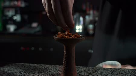 mouthpiece : Close-up of a mans hand that puts fruit tobacco in a bowl for a hookah. Preparation of hookah tobacco for Smoking. Modern hookah bar. Stock Footage