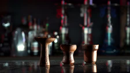 mouthpiece : Three clay bowls for hookah in hookah bar on the counter on the background of glasses and hookahs. Hookah bowl with tobacco stuffed into it. Slow motion.