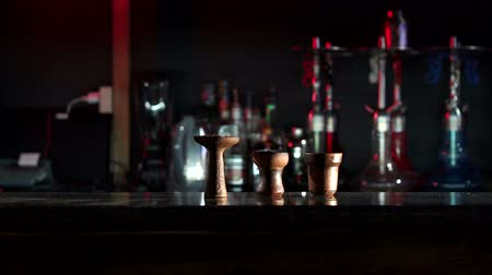 mouthpiece : A set of clay bowls for hookah of various shapes with fruit tobacco on the bar counter in the hookah bar, in the background there are many hookahs in the dark. Hookah flavor tobacco with hookah bowl. Stock Footage