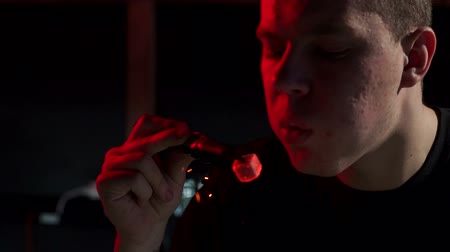 red square : Close-up of male bartender blowing on coals in hookah bar. Close-up of a man with tongs holding a burning coal and blowing on it. Slow motion. Stock Footage