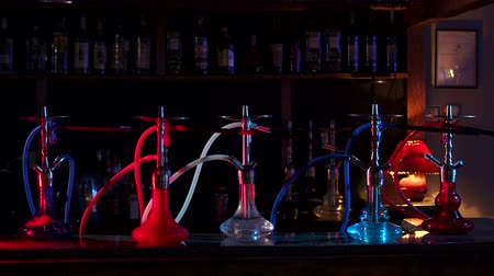 mouthpiece : A group of colorful hookahs stands on the bar counter in a modern hookah bar on a dark background. Hookah close-up on the background of the bar in the restaurant. Slow motion.