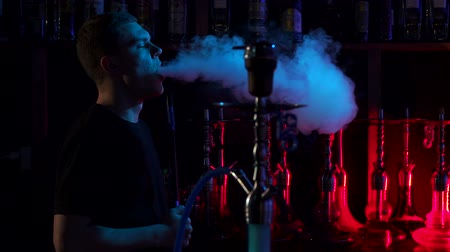 никотин : Confident man resting in lounge restaurant on against black background, smoking hookah. A young man smokes a hookah in a hookah bar on the background of a bar with hookahs in the dark, slow motion.
