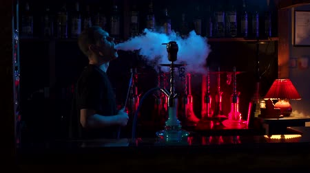 fuma : Silhouette of a young man in a hookah bar against the background of a bar with various colored hookahs, he smokes fruit tobacco and blows a lot of smoke. Slow motion. A man smokes a hookah.