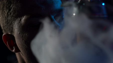 fuma : Silhouette of a young man Smoking a hookah in the dark, slow motion. Close-up. Close-up of a man Smoking a hookah on a black background.