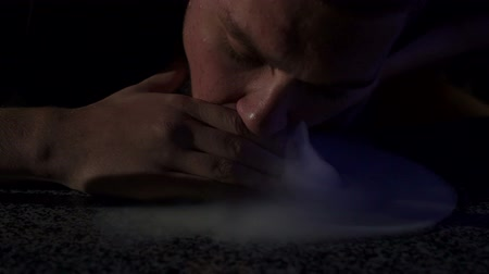 imbir : Close-up of a man blowing a lot of smoke on a table on a black background, slow motion. Silhouette of a man Smoking a hookah in the dark.