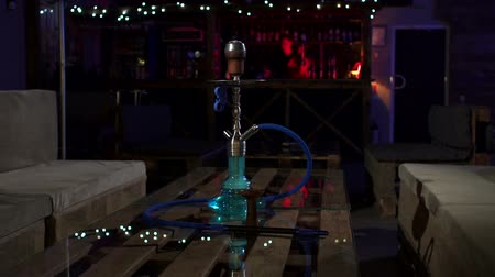 mangueira : A modern glass hookah stands on a table in a modern hookah bar, in the background flashing lights and a bar counter. Traditional Asian relaxation. A hookah standing on a table in a hookah lounge bar.