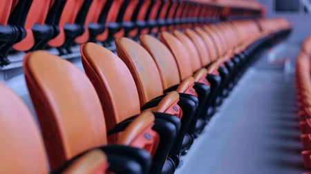 assentos : The empty orange or red chairs in the stands of the stadium. The stadium tribune. Empty stadium seats awaiting the spectators. Red chairs bleachers in large stadium.