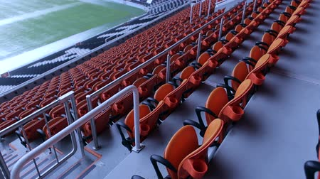arquibancadas : Stadium arena seats chair. Rows of orange spectator seating in a sports stadium. The empty orange or red chairs in the stands of the stadium. The stadium tribune. The view from the top.